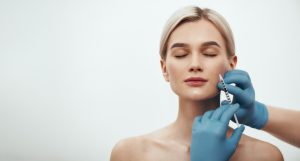 Young pretty woman keeping her eyes closed while doctors hand making an injection in her face. Horizontal web banner. Studio shot. Beauty concept